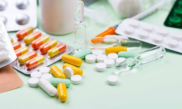 Diversas capsulas das cores amarelas, verdes, brancas e vermelhas em cima de uma mesa