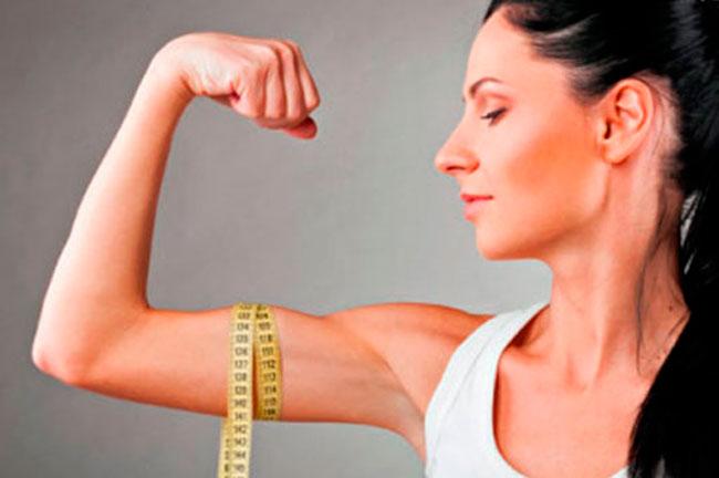 Mulher fazendo força no braço com uma fita de medidas