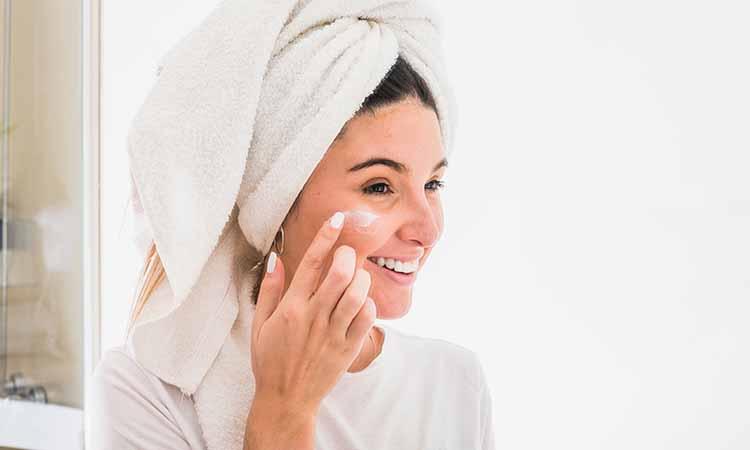 mulher com toalha na cabeça sorrindo e com uma das mãos no rosto colocando creme na bochecha