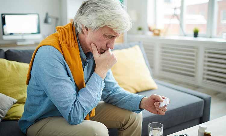 senhor sentado em um sofá com uma das mãos no rosto e a outra segurando uma cartela de medicamento
