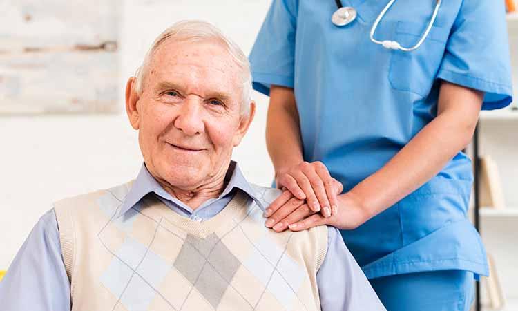 duas pessoas na imagem, um idoso sentado e uma mulher em pé com jaleco azul