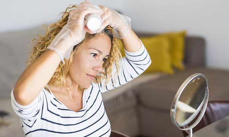 Mulher aplicando minoxidil nos cabelos