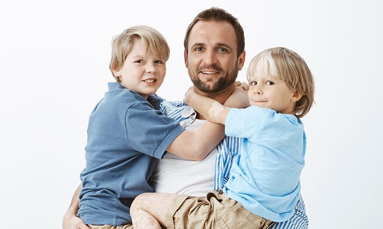 um pai segurando no colo dois meninos