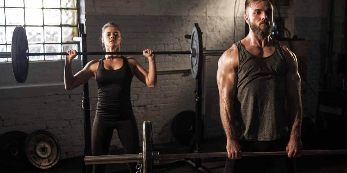 casal em uma academia puxando peso