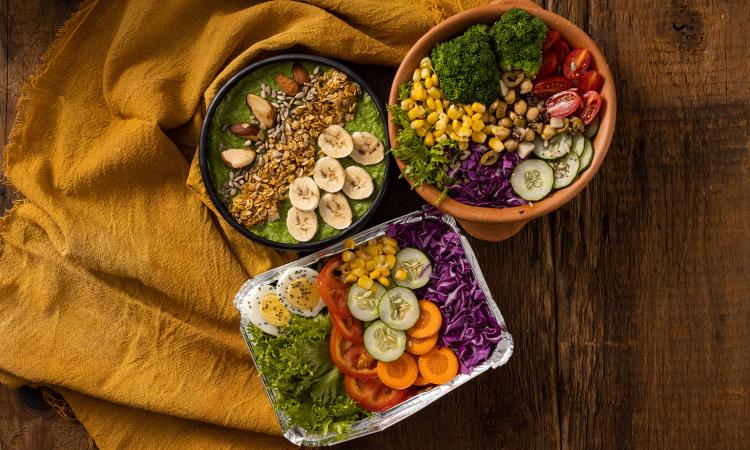 mesa com três potes com comidas como verduras, frutas, sementes juntas