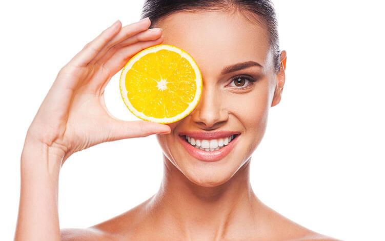 mulher sorrindo com os cabelos presos, com uma laranja perto do olho
