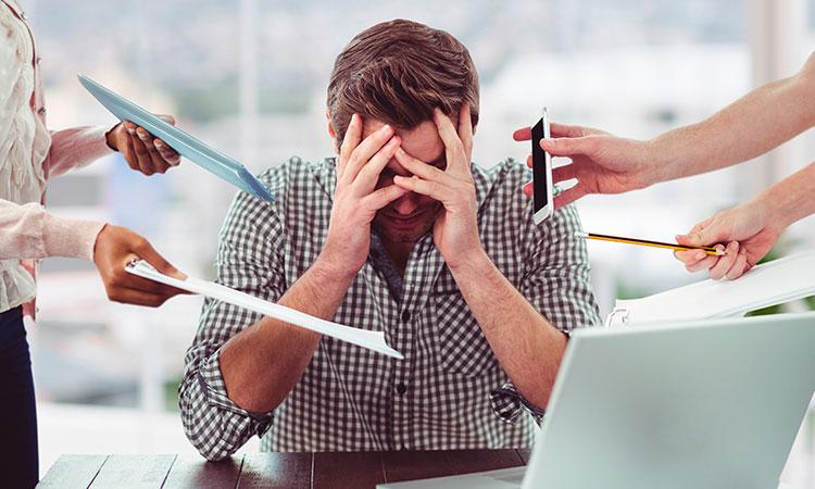 Pessoa cobrindo o rosto com as mãos pelo excesso de atividades a se fazer.