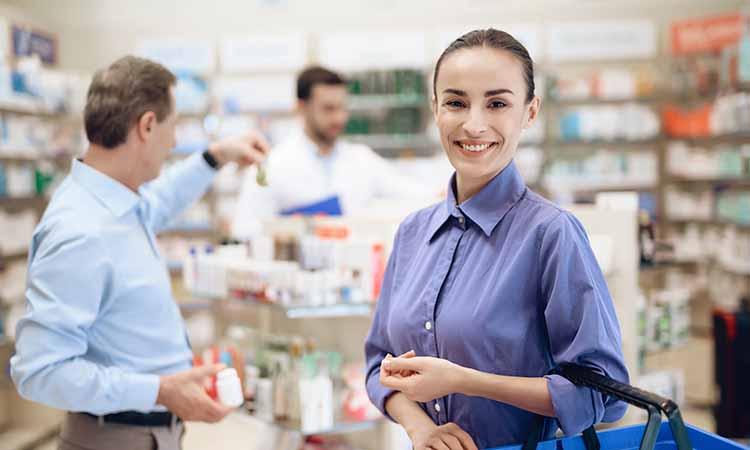 mulher de camisa roxa dentro de uma farmácia com uma sacola azul no braço