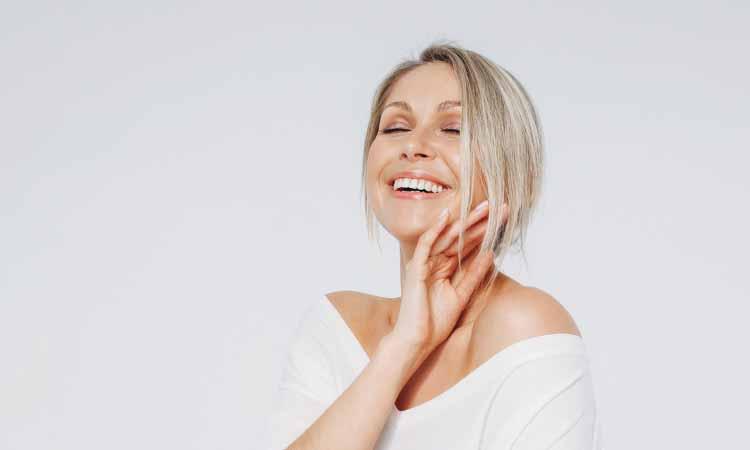 Mulher com mais idade sorrindo com uma das mãos no rosto