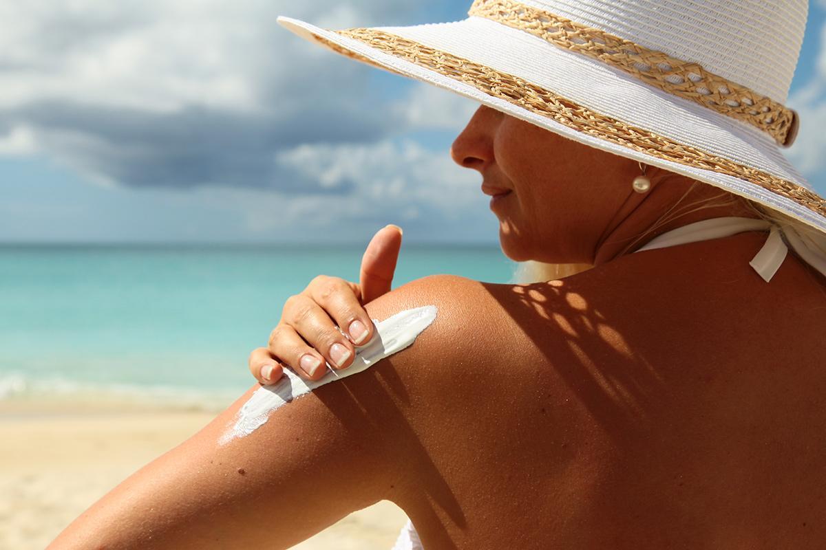 mulher de biquini na praia de costas passando protetor solar no braço