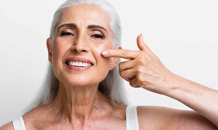 mulher com mais idade sorrindo com a mão no rosto