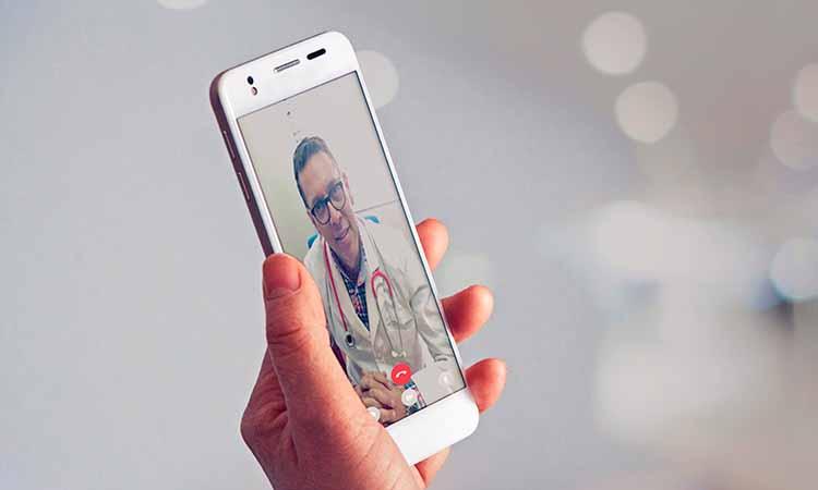 Mão segurando um celular com a chamada de video de um médico