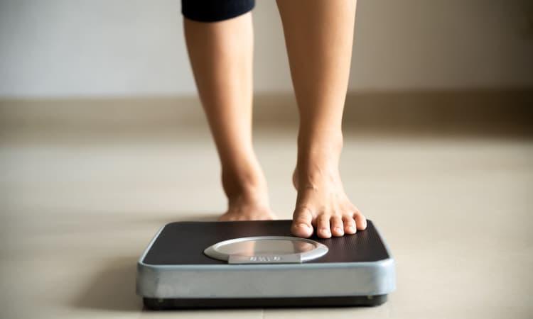 Pessoa usando uma balança para medir seu peso