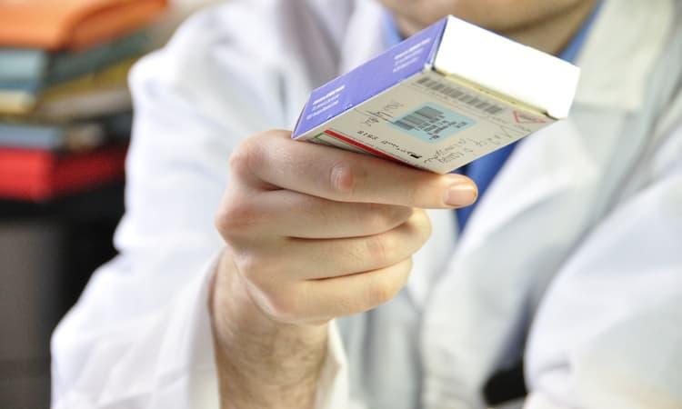 mão de um homem segurando uma caixa de medicamento