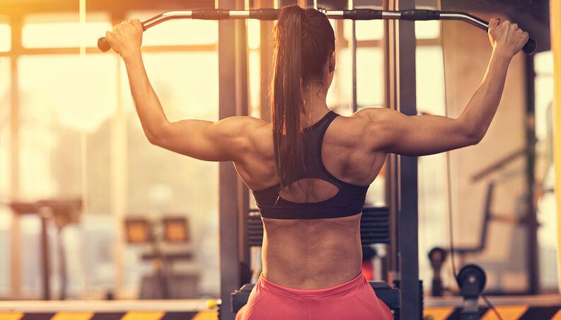 mulher com roupa de academia fazendo musculação