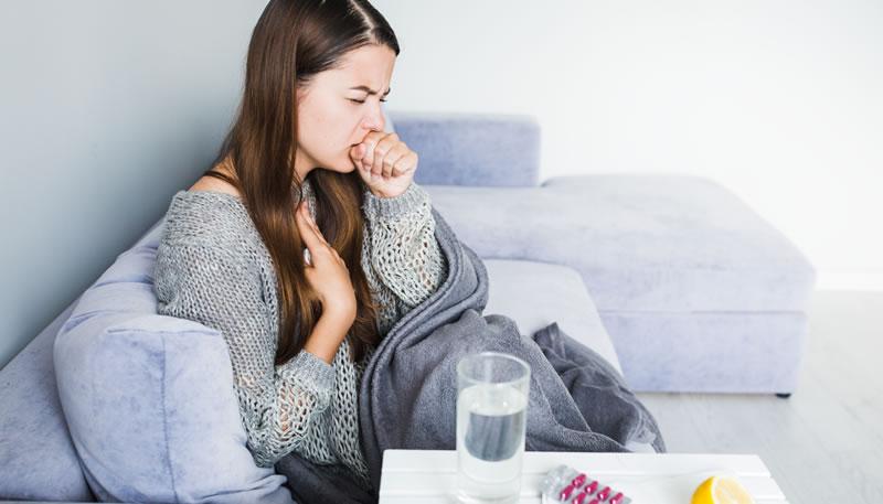 mulher sentada no sofá tossindo com copo de agua e remedio em cima da mesa