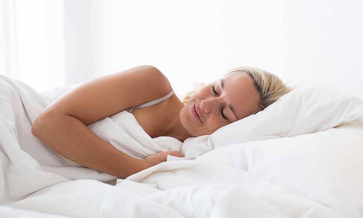 Mulher de olhos fechados deitada em uma cama com coberta e travesseiro