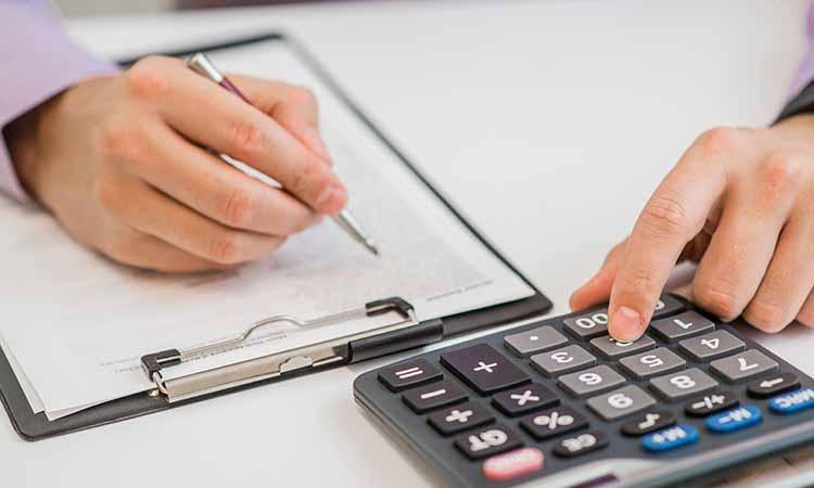 Mãos de um homem em cima de uma prancheta segurando uma caneta e tocando em uma calculadora