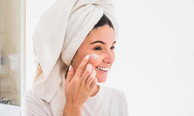mulher com toalha na cabeça colocando com uma das mãos um creme branco no rosto