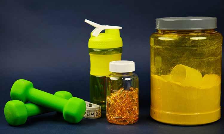 alteres verdes, fita de medida, garrafa de água, pote de suplemento e pote com capsulas amarelas dentro