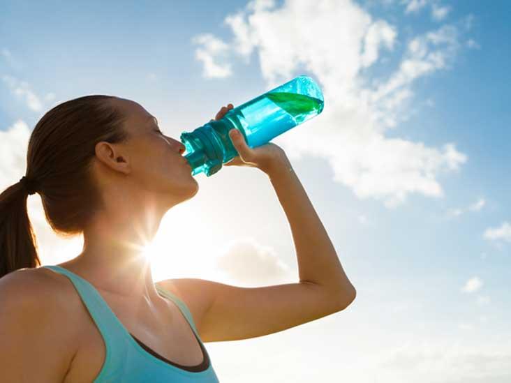 mulher com roupa de academia bebendo água