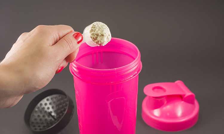 garrafa de suplemento rosa com um scoop de suplemetação