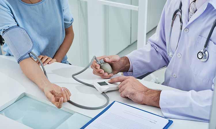 Uma mulher e um médico medindo a pressão