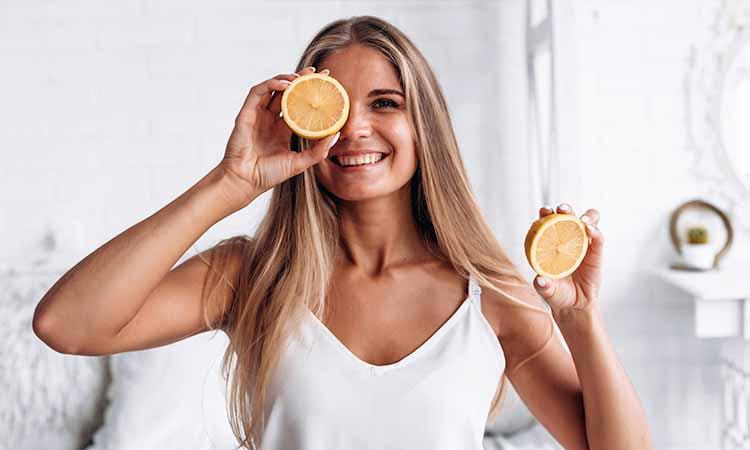 Mulher loira com cabelos compridos segurando nas duas mãos uma laranja cortada no meio