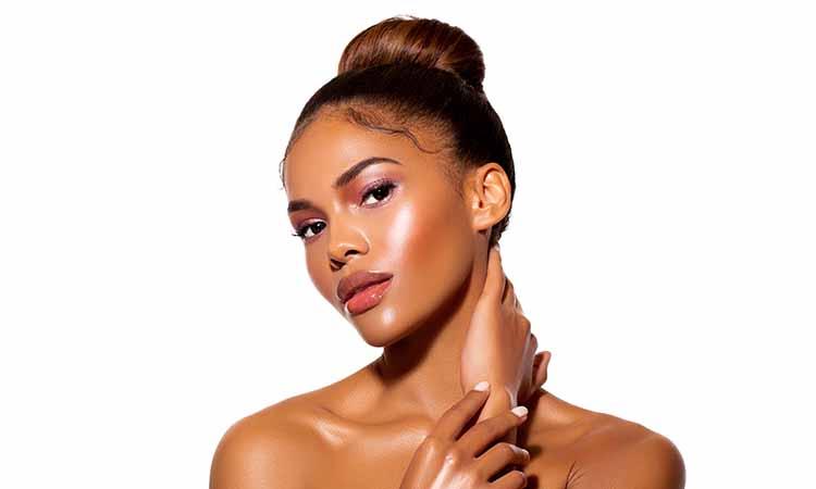 Mulher negra, com os cabelos presos, com as mãos no pescoço, usando maquiagem leve cor de rosa