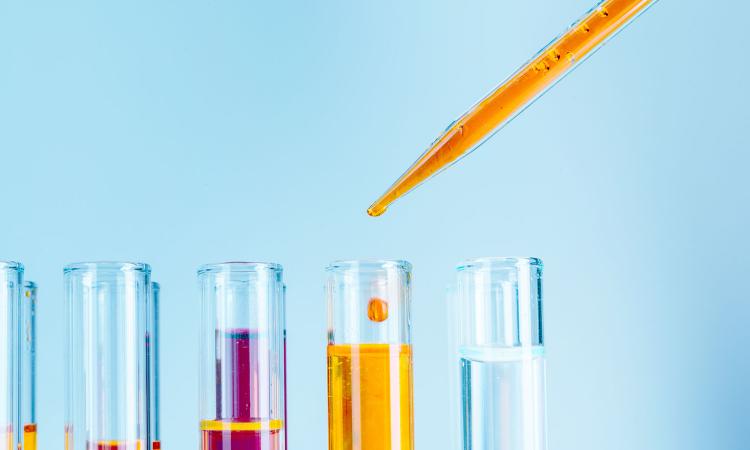 imagem de tubos de ensaio com um conta gotas com liquidos em rosa e laranja