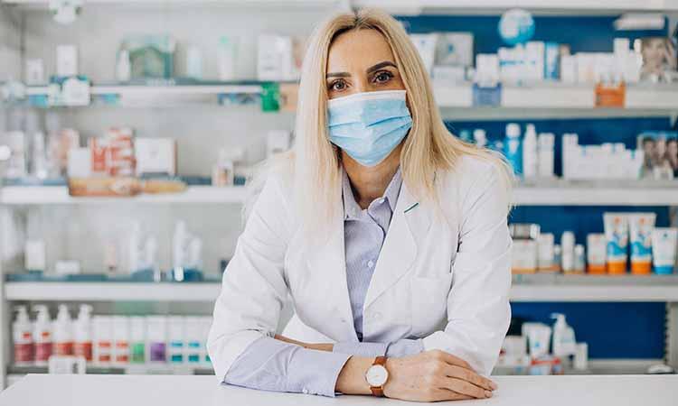 Mulher loira com jaleco branco de mascara com diversos medicamentos na prateleira