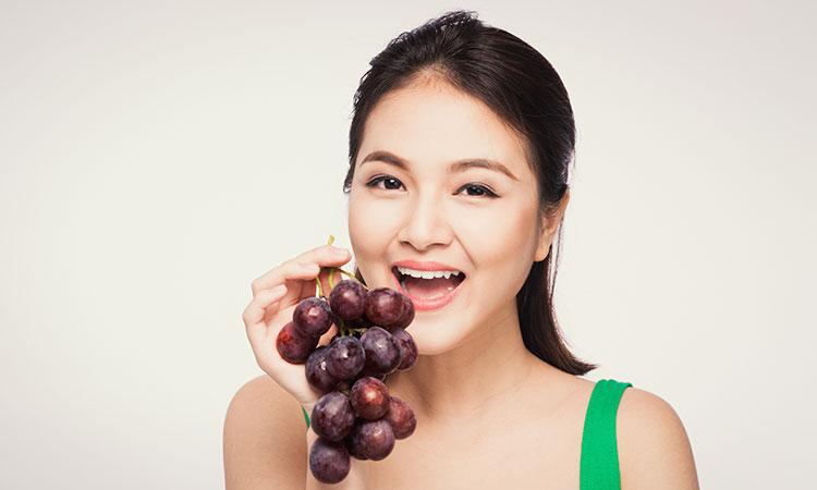 Mulher com cabelos preso segurando um cacho de uva com a boca aberta