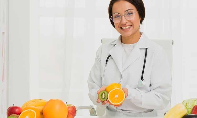 Mulher de cabelos presos com jaleco branco segurando frutas como laranja, kiwi e maça