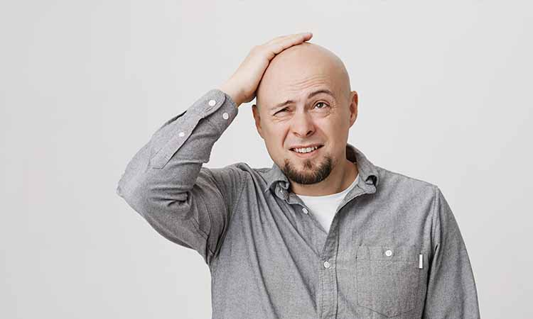 Homem com a camiseta cinza com a mão na cabeça calva