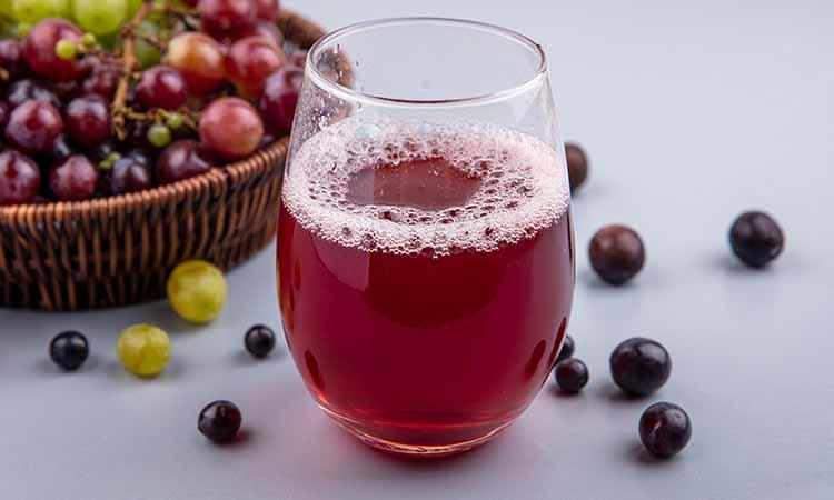 copo cheio de suco de uva com diversas uvas jogadas ao redor