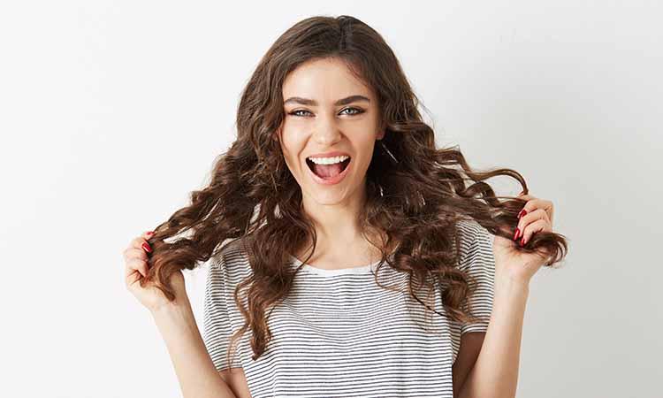 mulher com feição de feliz com as mãos no cabelo