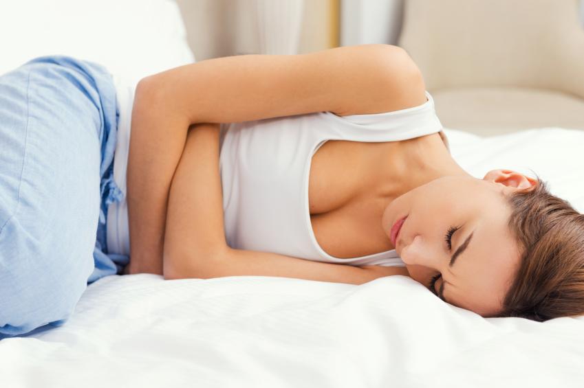mulher deitada na cama com as mão na barriga sentindo desconforto