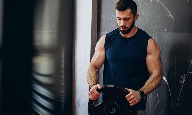Homem segurando um alter de peso com roupa de academia