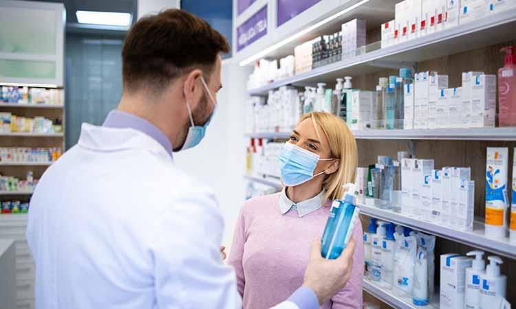 duas pessoas de mascara dentro de uma farmácia