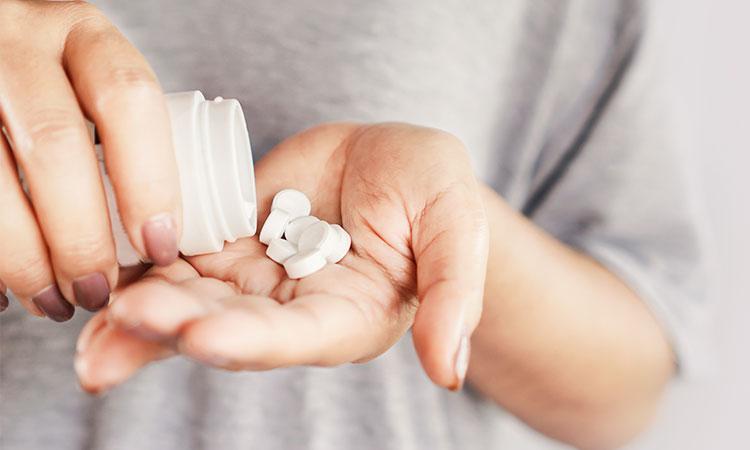 comprimidos de termogênicos sendo postos em uma mão.