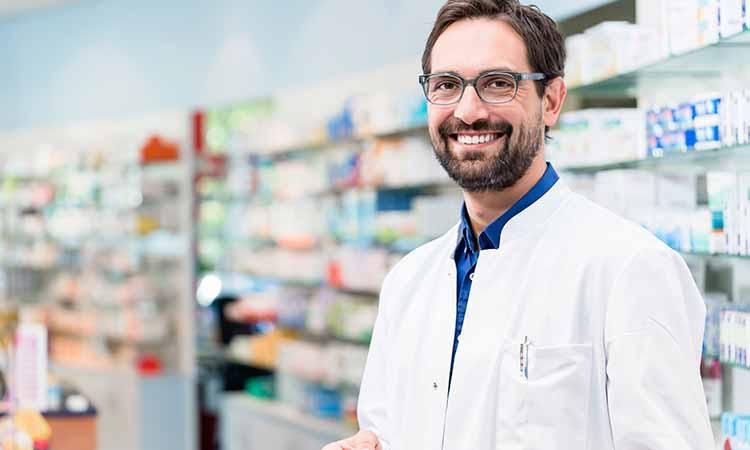 Homem com jaleco branco sorrindo e de oculos