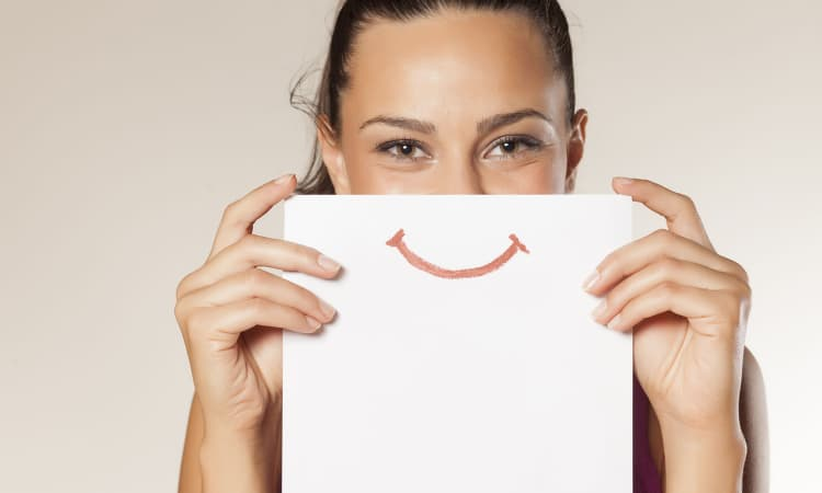 Mulher segurando um desenho de um sorriso na frente do rosto