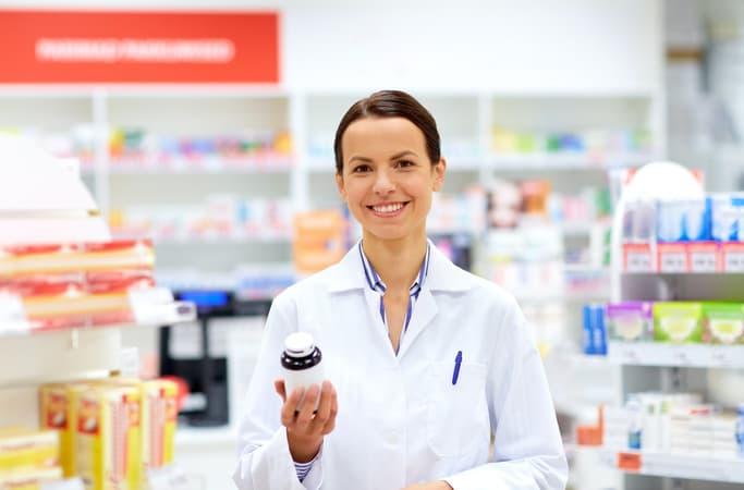 mulher com jaleco segurando um pote de medicamento na mão em uma farmácia de manipulação