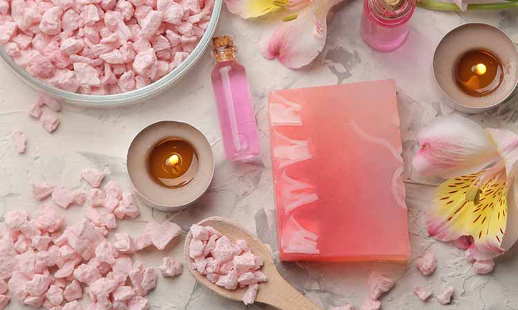 pote branco com quadrados rosas dentro e por volta da mesa, duas velas acessas, um tablete rosa, uma flor e um vidro transparente com o liquido rosa