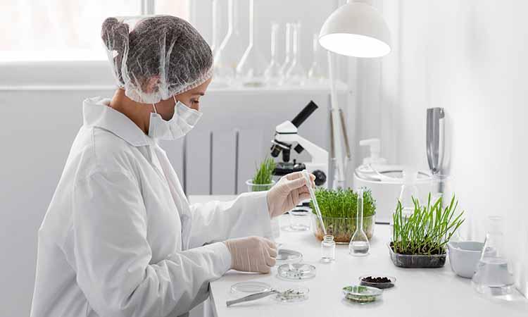 Mulher segurando um pinça com diversas plantas, potes e liquidos em cima de uma mesa