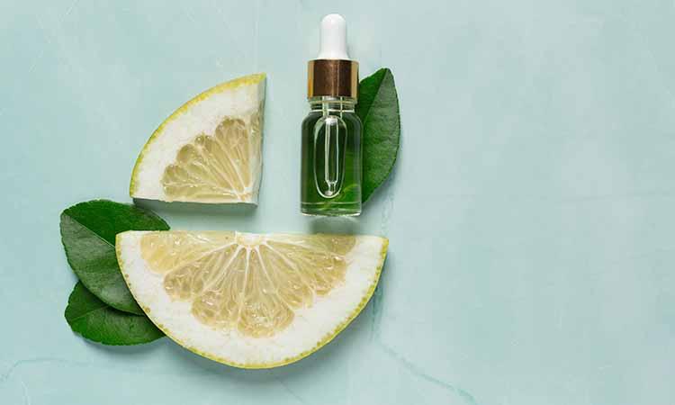 Duas fatias de laranja junto com um vidro transparente com liquido verde dentro e folhas verdes