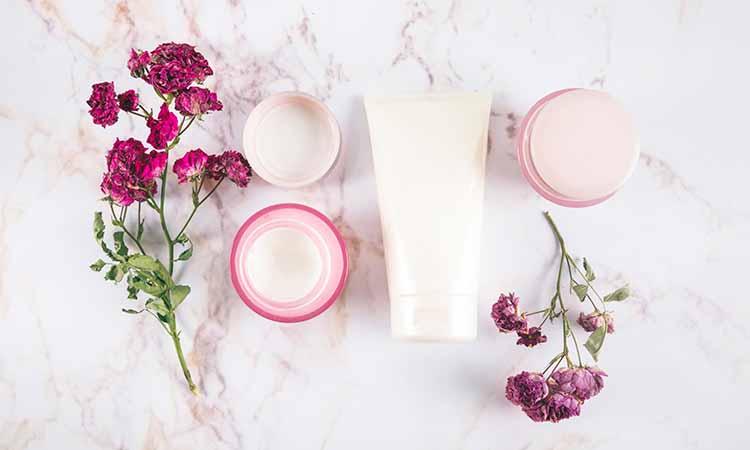 potes de cremes cor de rosa com flores rosas