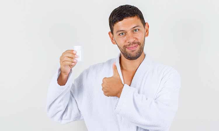 Homem com um roupão branco, segurando em sua mão direito um pote branco e na mão esquerda o dedão se encontra levantado