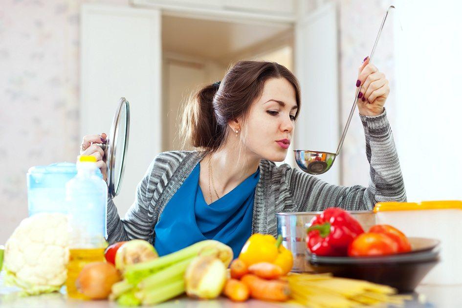 mulher em uma cozinha segurando uma tampa de panela e pegador com diversos alimentos em cima da mesa