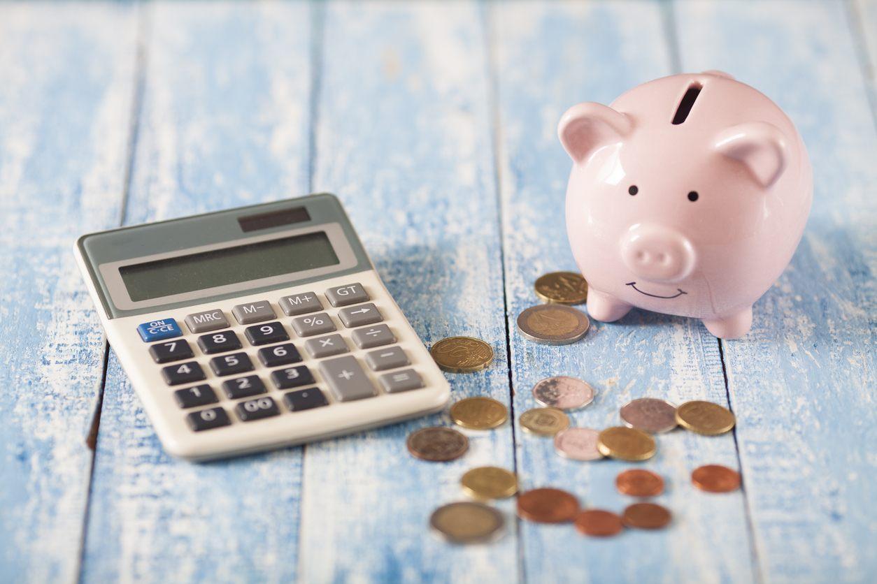imagem com um porquinho rosa como cofre, uma calculadora e diversas moedas ao redor